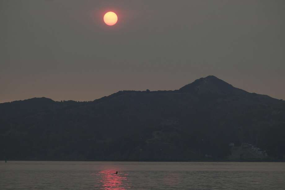 A rower goes past Angel Island and the sun rising behind in smoke from wildfires Wednesday, Aug. 19, 2020, in Sausalito, Calif. Thousands of people were under orders to evacuate in regions surrounding the San Francisco Bay Area Wednesday as nearly 40 wildfires blazed across the state amid a blistering heat wave now in its second week. Smoke blanketed the city of San Francisco. Photo: Eric Risberg/Associated Press / Copyright 2020 The Associated Press. All rights reserved