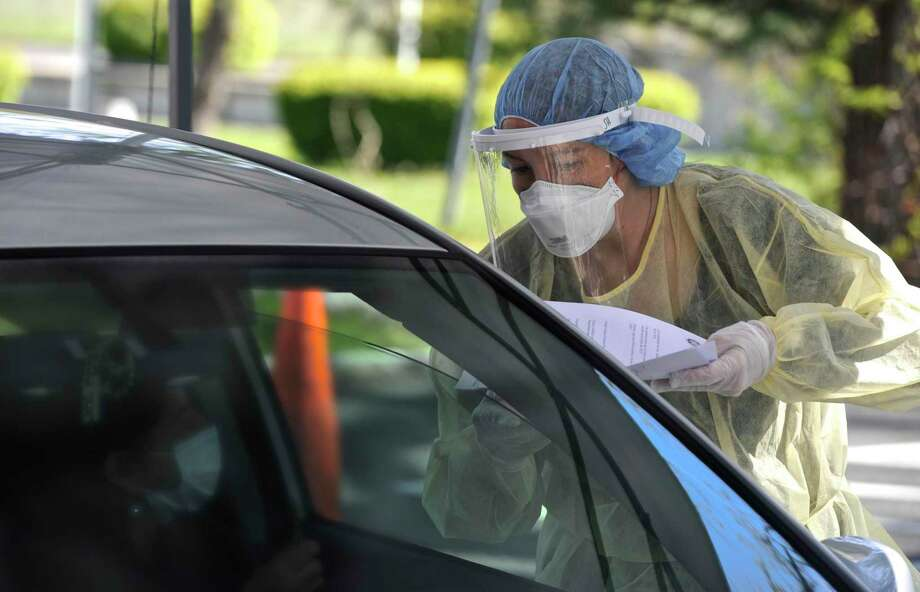 Jolene Henion, left, an NPRN with the Greater Danbury Community Health Center, hands back paperwork at a drive-thru vaccine clinic was held at Rogers Park Middle School on Thursday, May 14, 2020, in Danbury, Conn. Free, drive-thru testing for COVID-19 will be offered on Saturday, Aug. 22 at Rogers Park Middle School Photo: H John Voorhees III / Hearst Connecticut Media / The News-Times