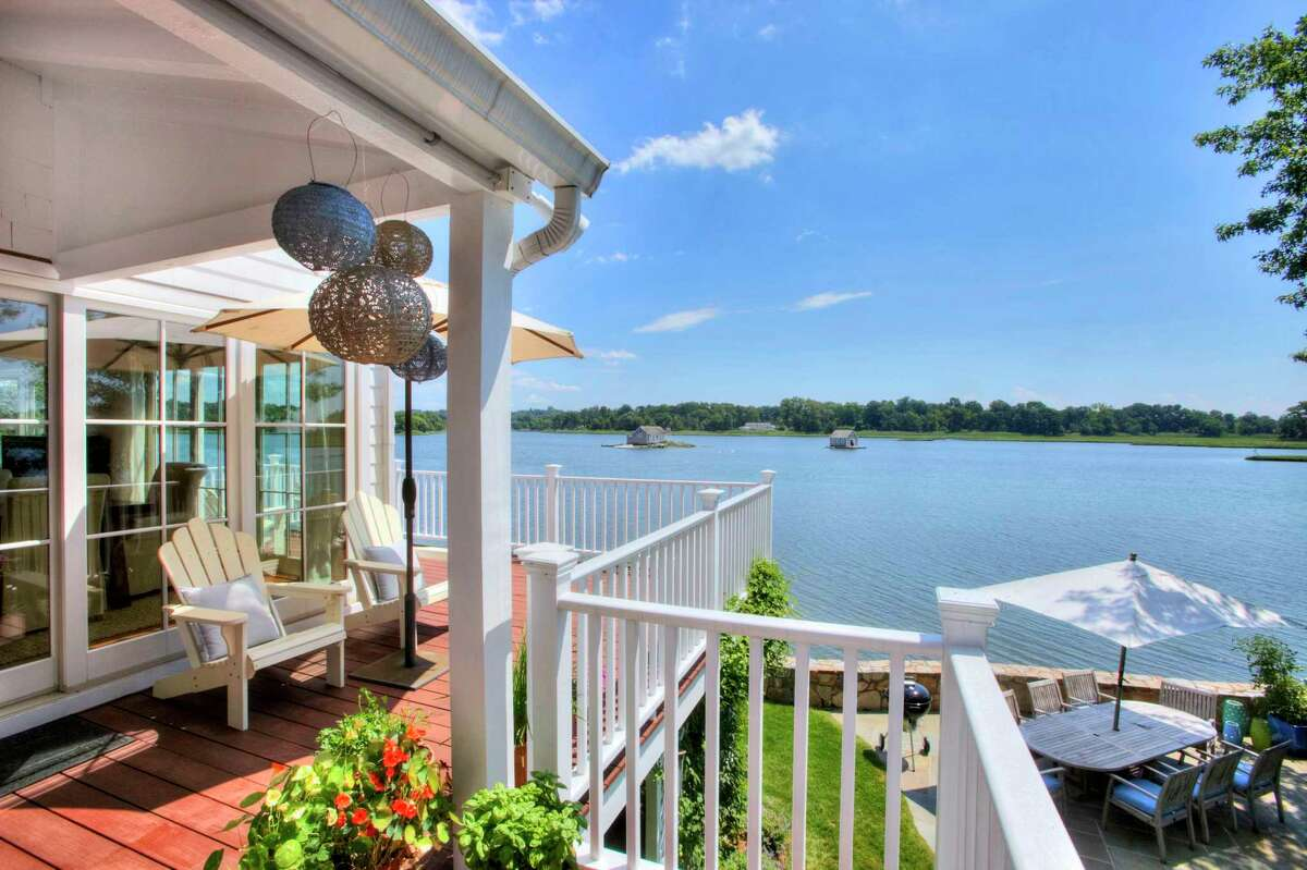 The wrap-round deck enjoys water views and looks down on the bluestone patio. One need only view the trellis teeming with blush pink roses in bloom seemingly propping up the deck to get a sense of this property's beauty.