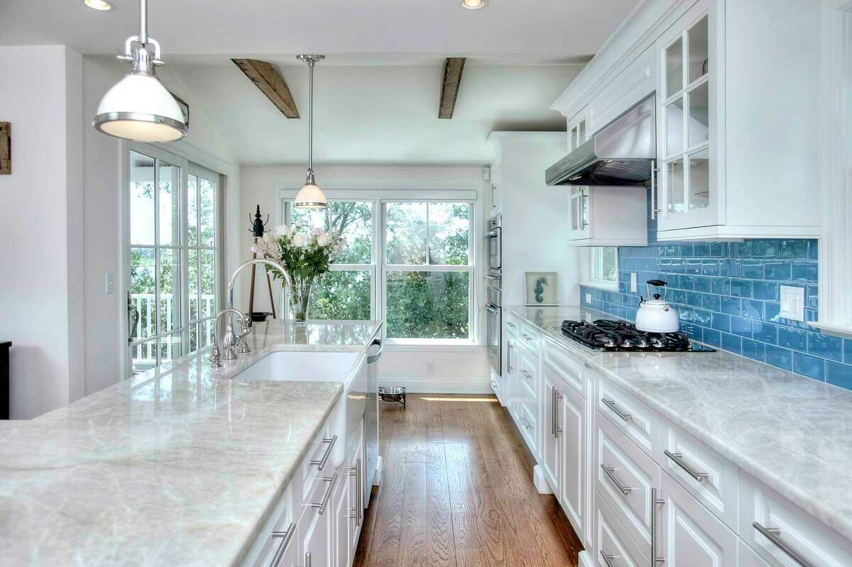The gourmet kitchen features a long L-shaped center island, farm sink, walk-in pantry, wet bar, a wine refrigerator and high-end appliances.