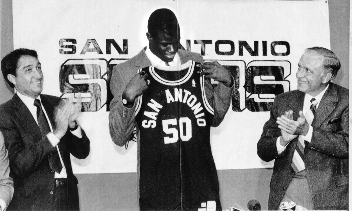 SAN ANTONIO, TEXAS, NOV. 6. David Robinson holds up his new jersey as he is welcomed to the San Antonio Spurs by Mayor Henry Cisneros, left, and Spurs Chairman Angelo Drossos. The former Navy center still has a two year commitment to the Navy, but the team is eagerly awaiting his help. AP LASECOLOR STF-David Breslauer) 1987