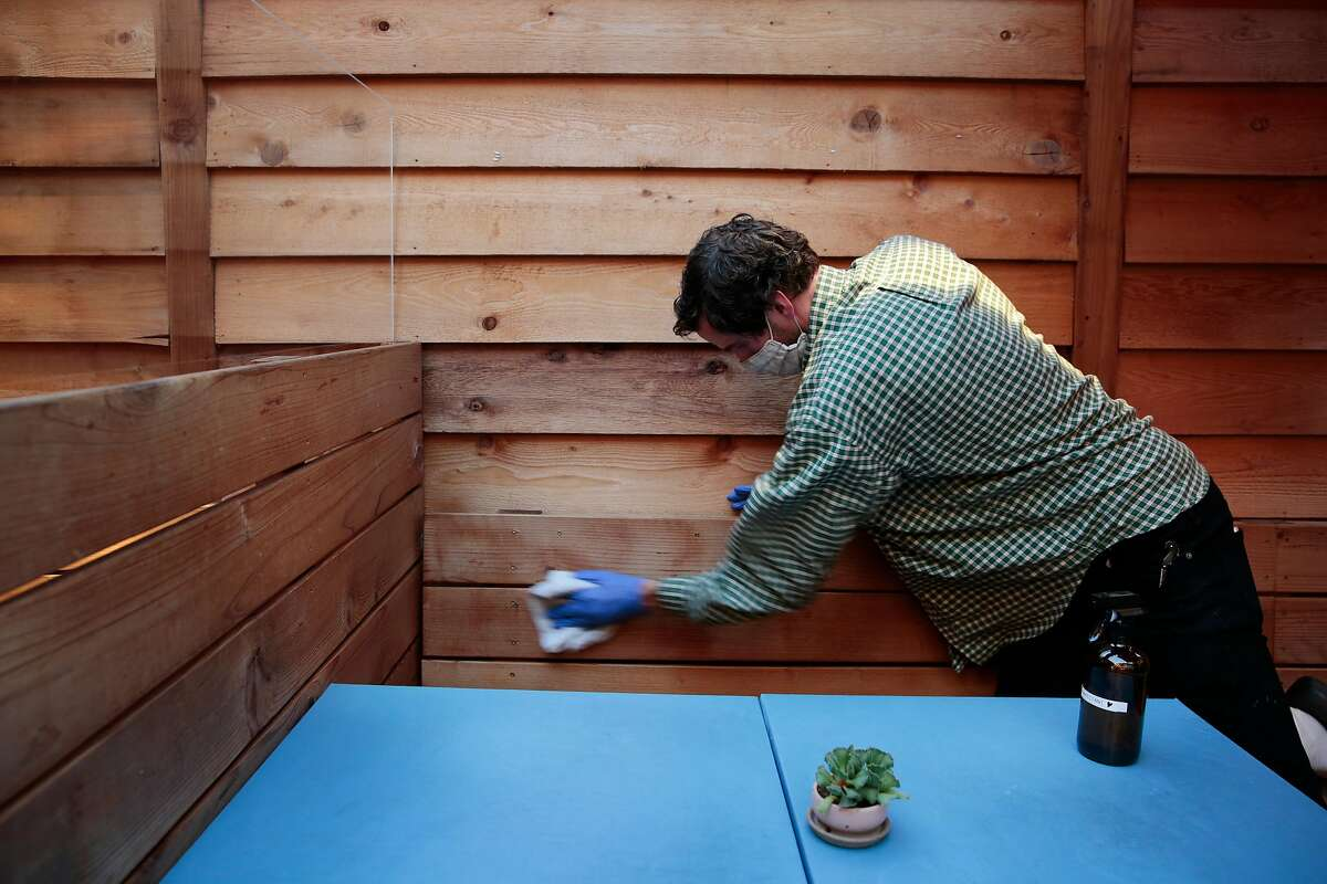 General manager Den Stephens disinfects a booth at North Light, a restaurant in Oakland, in August.