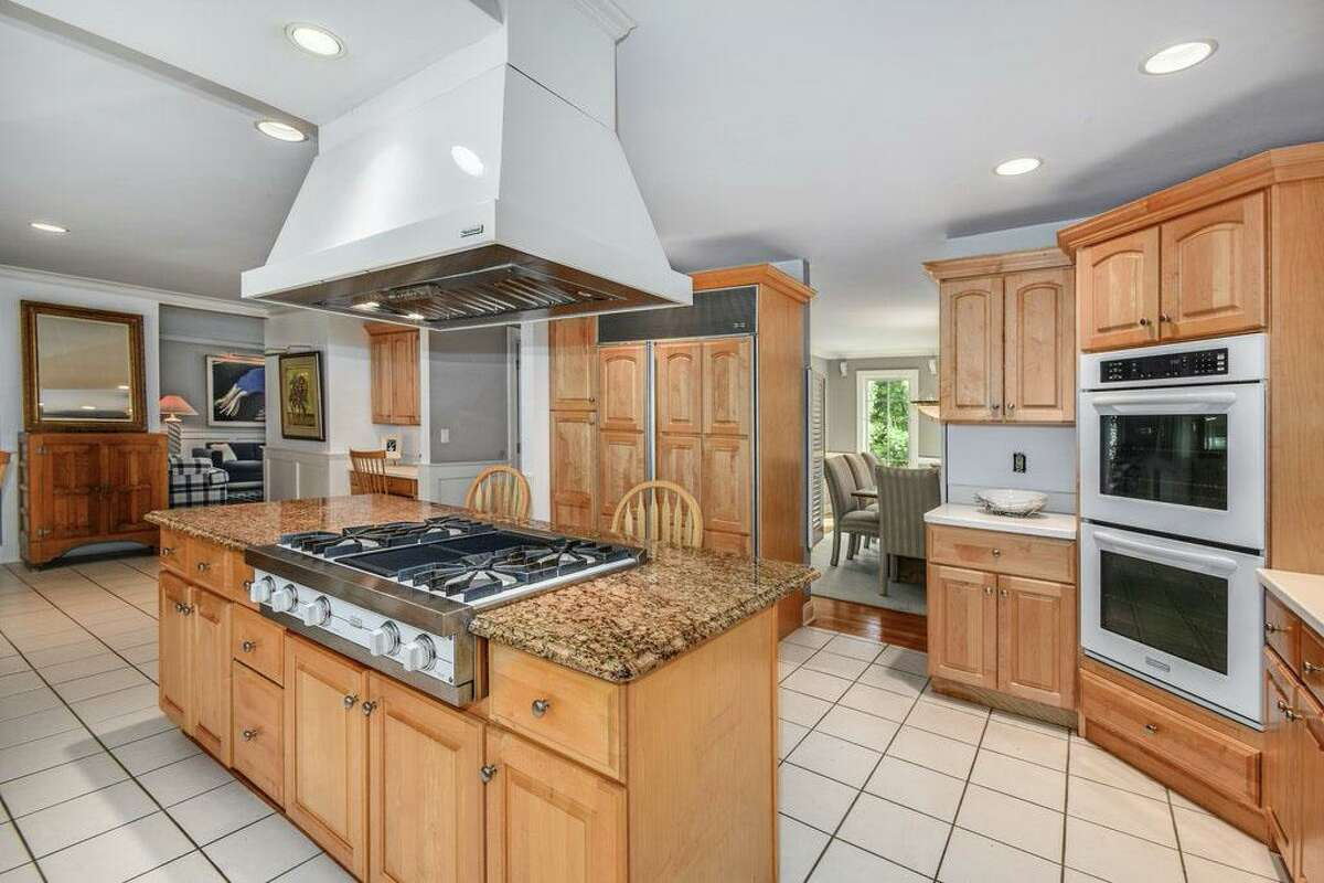 In the spacious eat-in chef's kitchen there is a center island/breakfast bar topped in granite, Corian counters, a built-in desk area and high-end appliances. Open to the kitchen is the family or great room, which has a gas-fueled marble fireplace, a wall of floor-to-ceiling bookshelves, chair railing, and a deep tray ceiling. The flow between these two rooms and the backyard make this house a great place for indoor-outdoor living and entertaining. And if its two-acre parcel is not enough for the next owners they should consider that the town has a reverence of protected land.