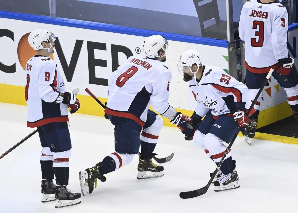 Washington Capitals left wing Alex Ovechkin (8) celebrates his teams win with teammate Radko Gudas (33) after defeating the New York Islanders during third period NHL Eastern Conference Stanley Cup playoff hockey action in Toronto on Tuesday, Aug/ 18, 2020. (Nathan Denette/The Canadian Press via AP)
