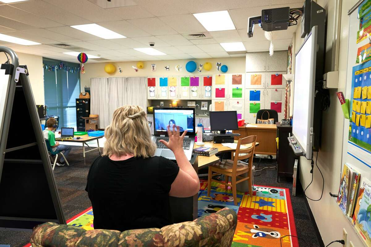 Emerson Elementary kindergarten teacher Callie Reams greets her students in the first day of school Wednesday, Aug. 19, 2020. The school year began with virtual learning. Reams' son, left, learns remotely while his mother teaches remotely.