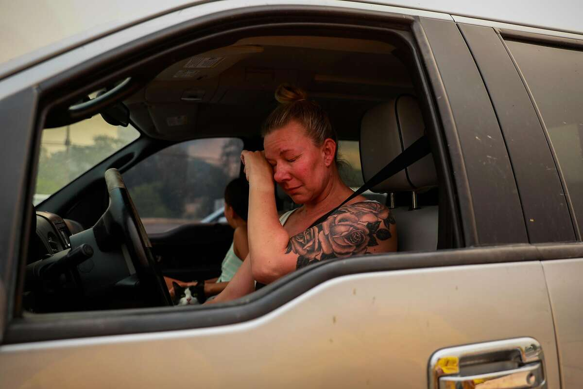 """Gina Santos cries in her car after evacuating the LNU Lightning Complex Fire in Vacaville , Calif., on Wednesday, August 19, 2020. She moved to her """"dream house"""" several months ago and was distraught that it might have burned down."""
