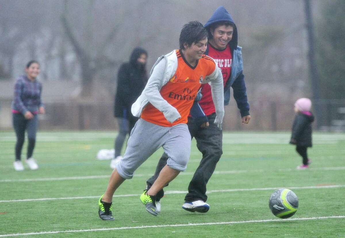 Christian Acero, left, and Jose Acero play soccer with their family at the Rogers Park football field in Danbury, Conn. on Saturday, Jan. 11, 2014.