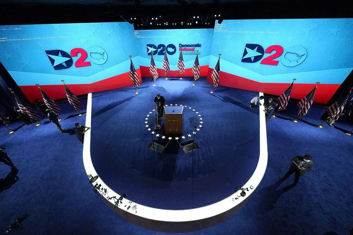 A worker vacuums the stage where Democratic vice presidential candidate Sen. Kamala Harris, D-Calif., will speak on third day of the Democratic National Convention, Wednesday, Aug. 19, 2020, at the Chase Center in Wilmington, Del. (AP Photo/Carolyn Kaster)