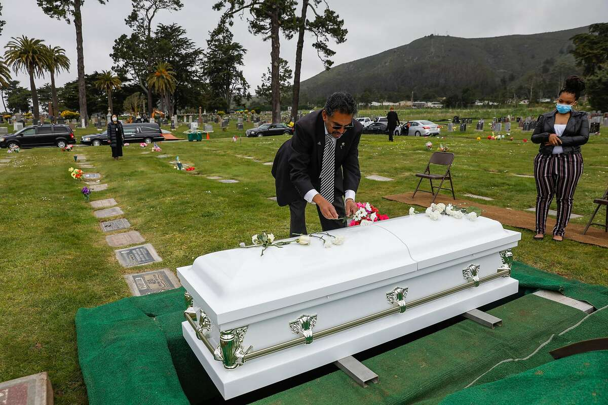 Funeral director Vaughn O. Nixon Sr. organizes flowers over the casket of Tessie Henry who died of Covid-19 at the age of 83 is buried on Wednesday, April 8, 2020 in Colma, California.