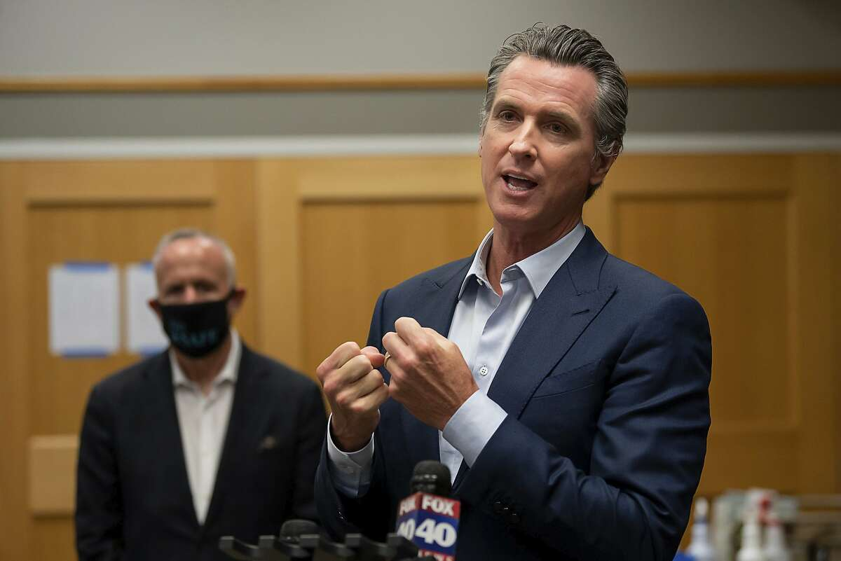 California Gov. Gavin Newsom speaks during a tour of a cooling center with Sacramento Mayor Darrell Steinberg at the Tsakopoulos Library Galleria on Tuesday, Aug. 18, 2020, in Sacramento, Calif. Newsom declared an emergency Tuesday over wildfires burning throughout California as the state's power grid operator pleaded with residents and businesses to continue conserving energy to avoid rolling blackouts. (Paul Kitagaki Jr./The Sacramento Bee via AP, Pool)