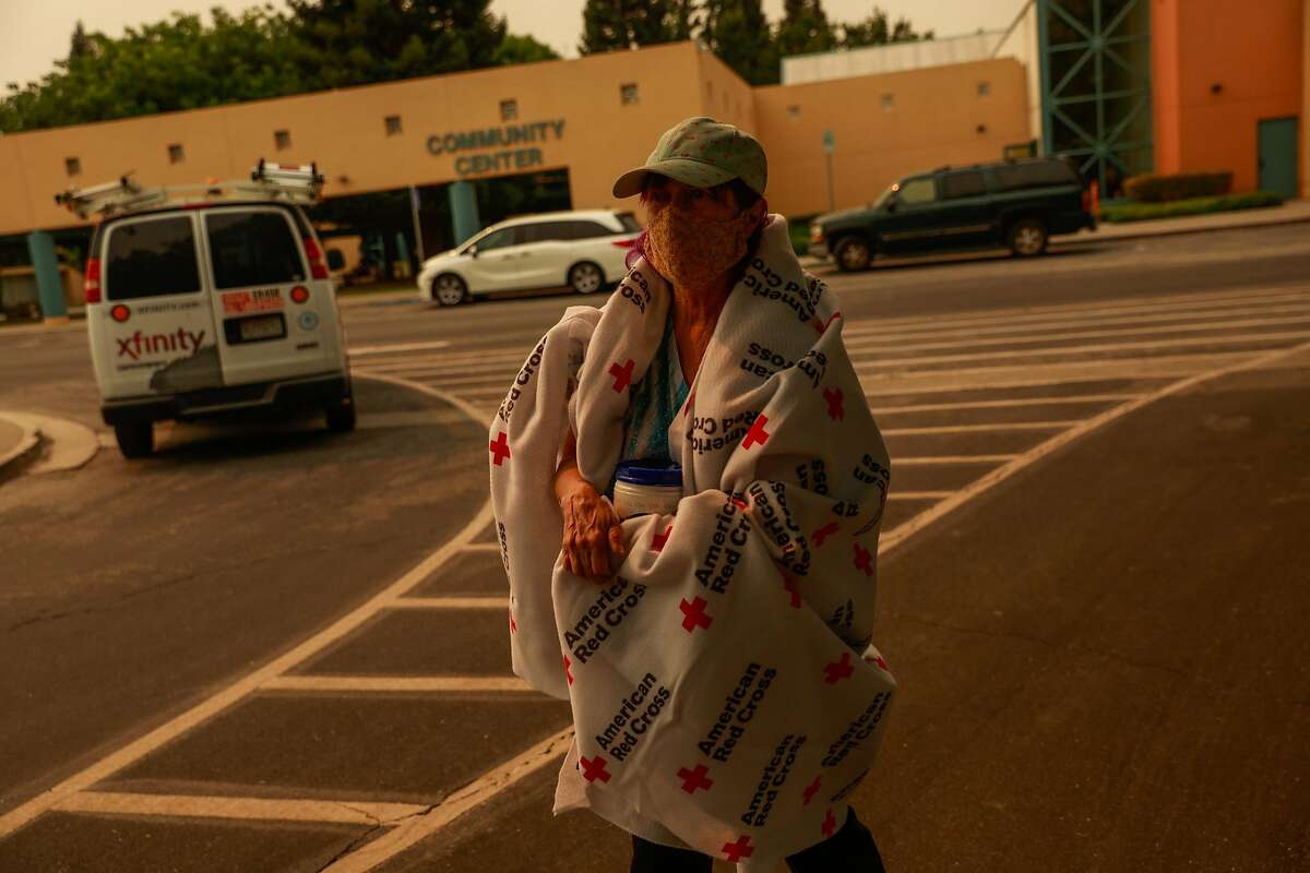 Evacuee Carol, 73, walks back to her car after picking up supplies at the Red Cross Shelter at the Ulatis Cultural Center after escaping the LNU Lightning Complex Fire in Vacaville , Calif., on Wednesday, August 19, 2020.