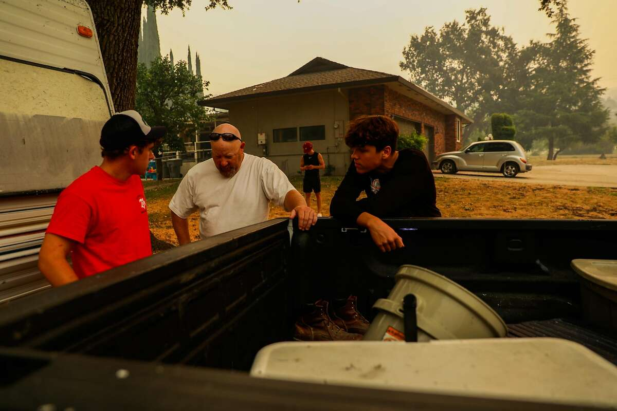 Jack Mitchell(left), Tim Plowman (center) and Haedyn Gomes (right) chat as they prepare to evacuate the LNU Lightning Complex Fire in Vacaville , Calif., on Wednesday, August 19, 2020.