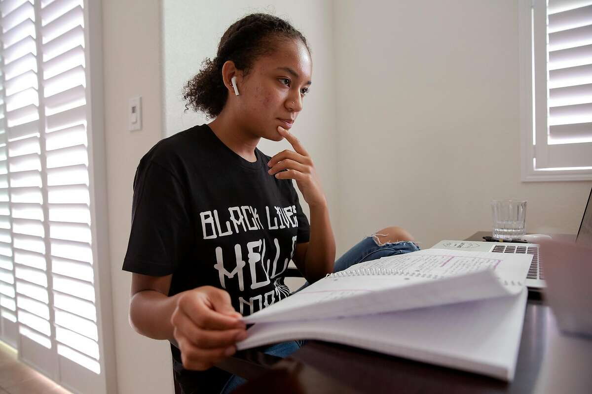 Aniyah Story looks through her notes during her Advanced Placement American History class at her home in San Leandro, Calif. on August 17, 2020. Story is an advocate for bill AB2016, which will make ethnic studies a graduation requirement for high school students. Currently lawmakers are divided over the bill, saying that while they agree ethnic studies should be expanded there is disagreement over what lessons the curriculum should include.