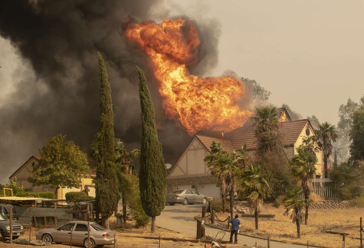 A man trying to save a home in Vacaville, Calif., watches futilely as it goes up in flames.
