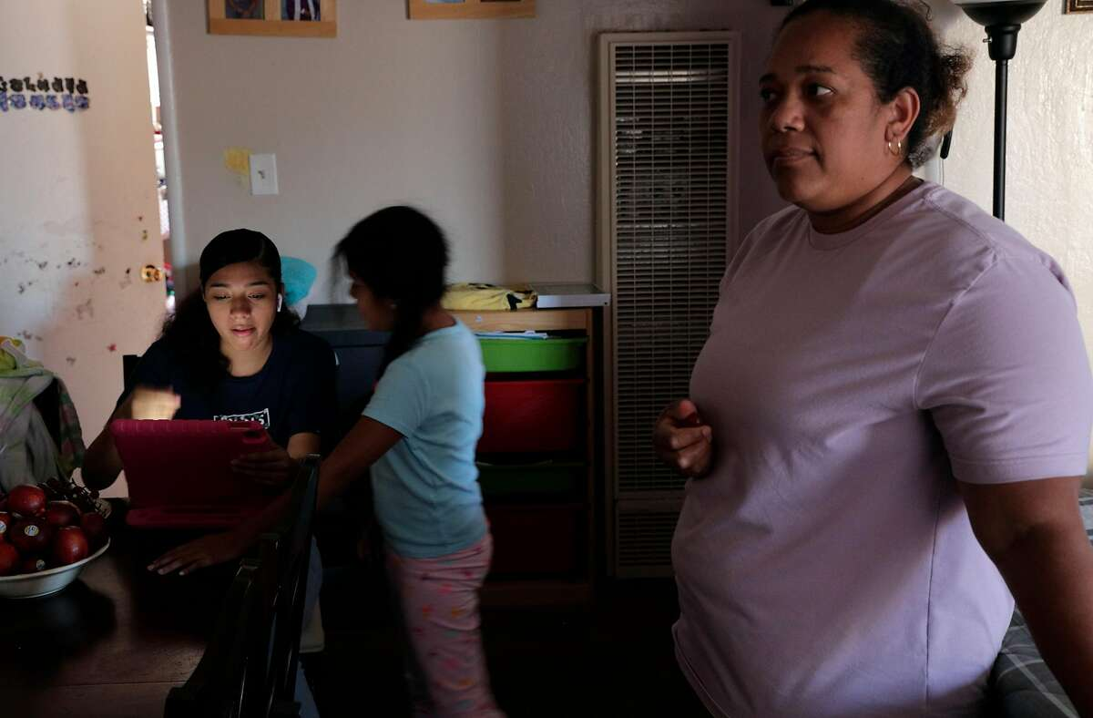 Elena Sabay, right, with her daughters, Johmara, 14, left, and Dayana, 7, right, as the Romero family spends time at home in Oakland, Calif., on Monday, July 13, 2020. Elena Sabay recently lost her job as hotel housekeeper because of business shutdowns and her husband's, Alfredo Romero, earnings are the only thing keeping the family afloat during the pandemic.