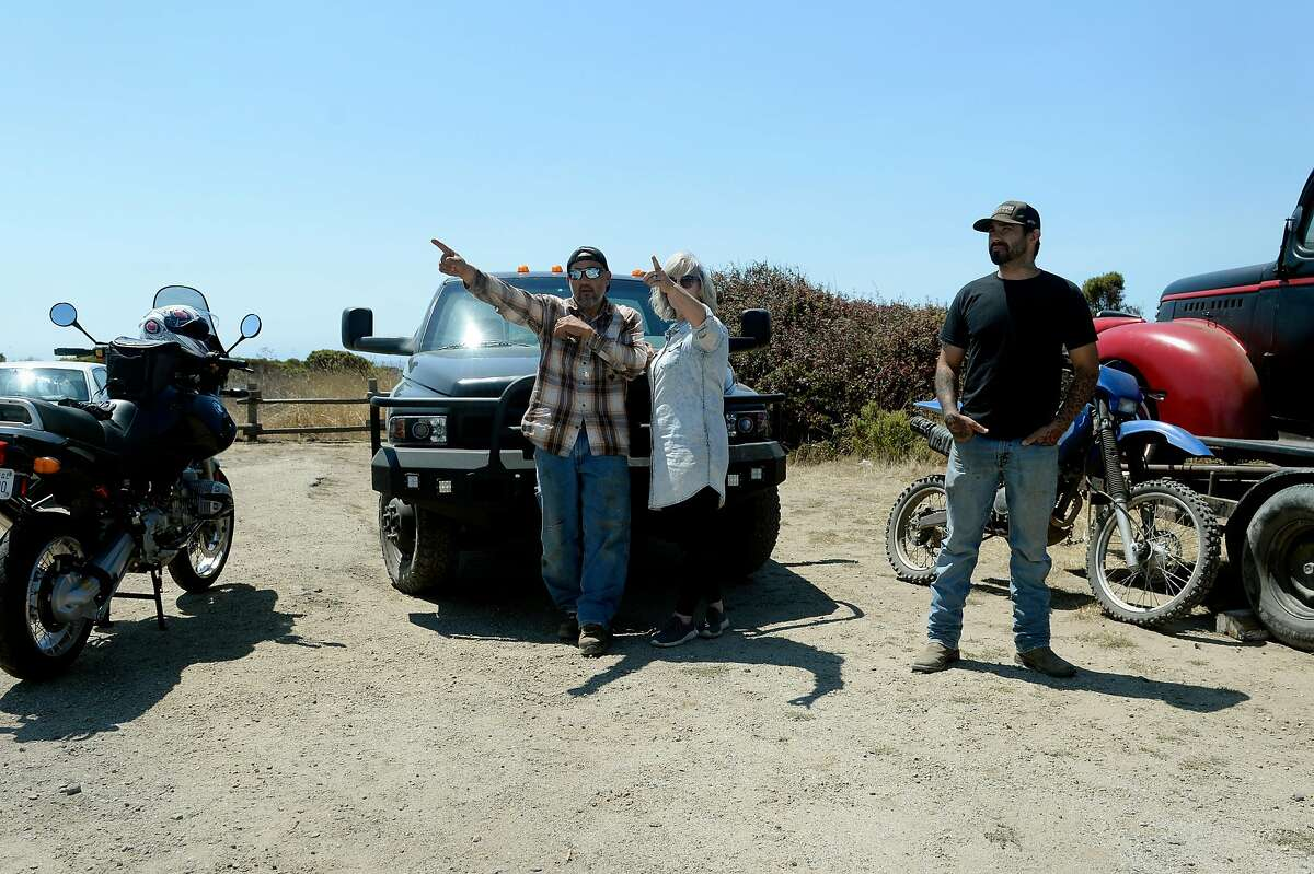 """""""Hoss,"""" left to right, his wife Janice McCargo-Viramontes and Marcel Dodge, all residents in Santa Cruz County, watch from a distance as a large wildfire burns on the hills near their homes on August 19, 2020, near Pescadero, Calif."""