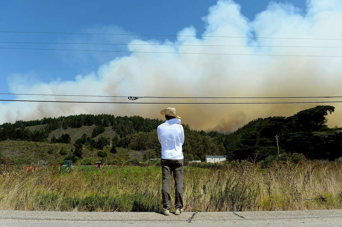 John Han watches the progress of a large wildfire as it pushes toward Bonny Doon and Santa Cruz County on August 19, 2020, near Pescadero, Calif. Han said he was there from the East Bay where he lives to help his friend, Gaby Lee, secure her shared farmland as best she could.