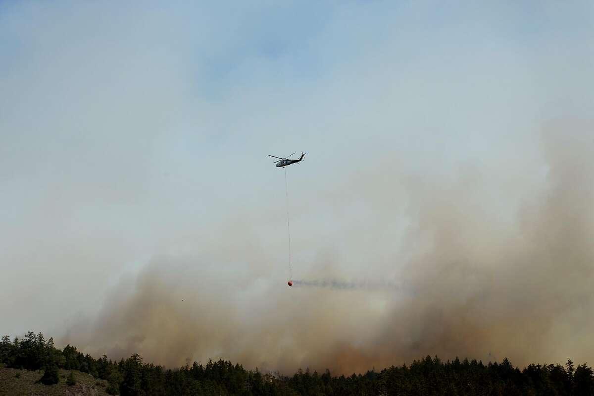 Fire crews haul fire retardant into another big wildfire as it pushes toward Bonny Doon and Santa Cruz County on August 19, 2020, near Pescadero, Calif.