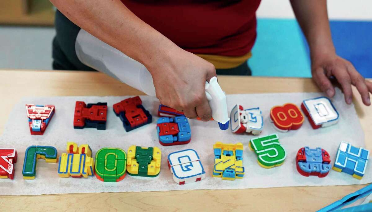 Pre-k teacher Monica Alvarez cleans and disinfects teaching tools as she prepares her classroom at Southside ISD last week. Most school districts have begun remote teaching but are delaying in-person instruction until Sept. 8 at the earliest. (AP Photo/Eric Gay)