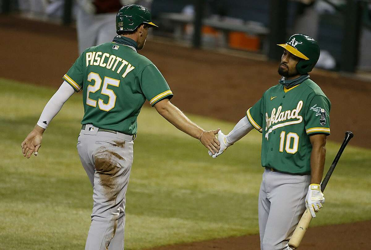 Oakland Athletics' Stephen Piscotty gets a high five from Marcus Semien after scoring their first run against the Arizona Diamondbacks during the second inning of a baseball game Tuesday, Aug. 18, 2020, in Phoenix. (AP Photo/Darryl Webb)