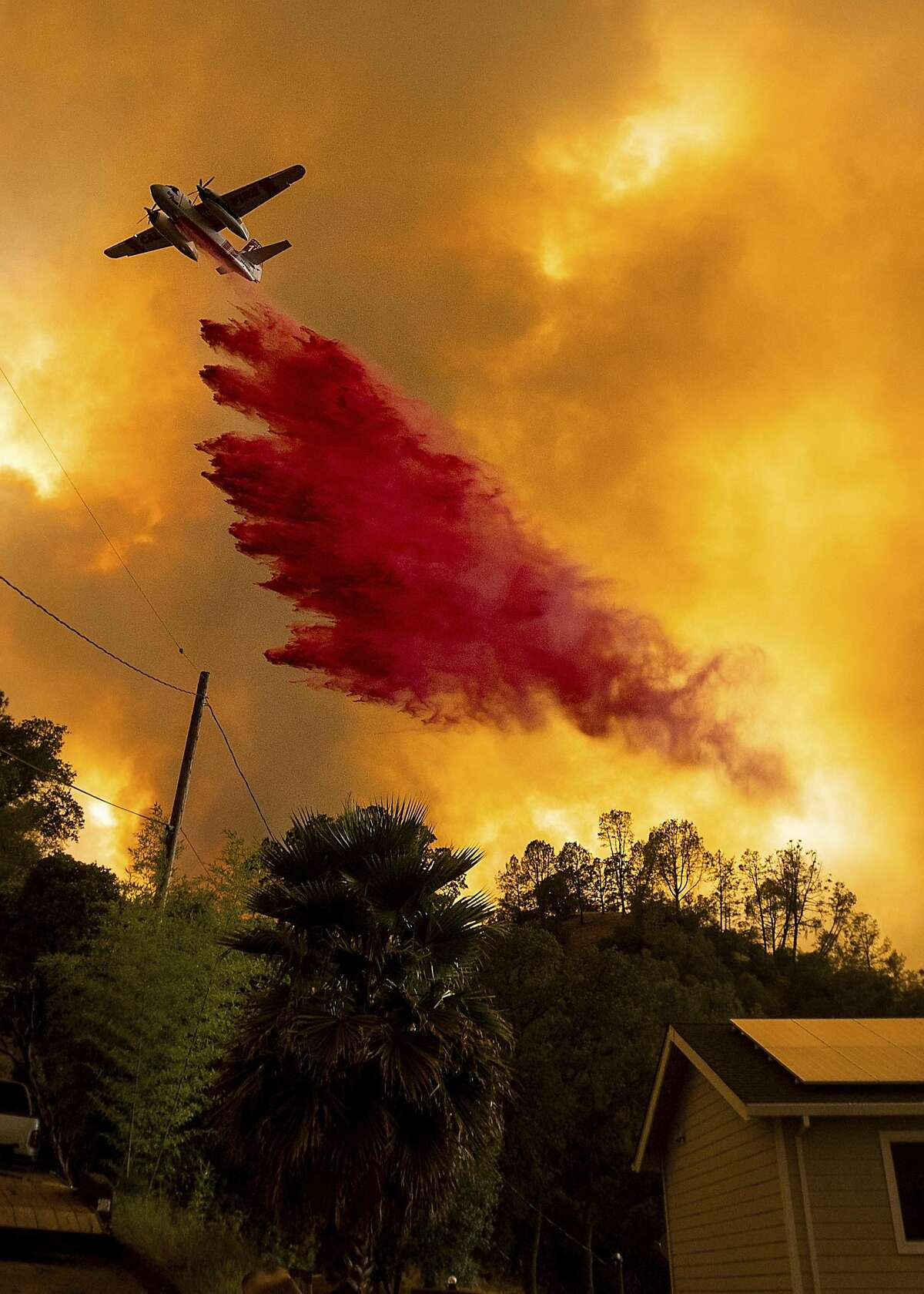 An air tanker drops retardant as the LNU Lightning Complex fires tear through the Spanish Flat community in unincorporated Napa County, Calif., Tuesday, Aug. 18, 2020. Fire crews across the region scrambled to contain dozens of wildfires sparked by lightning strikes as a statewide heat wave continues. (AP Photo/Noah Berger)
