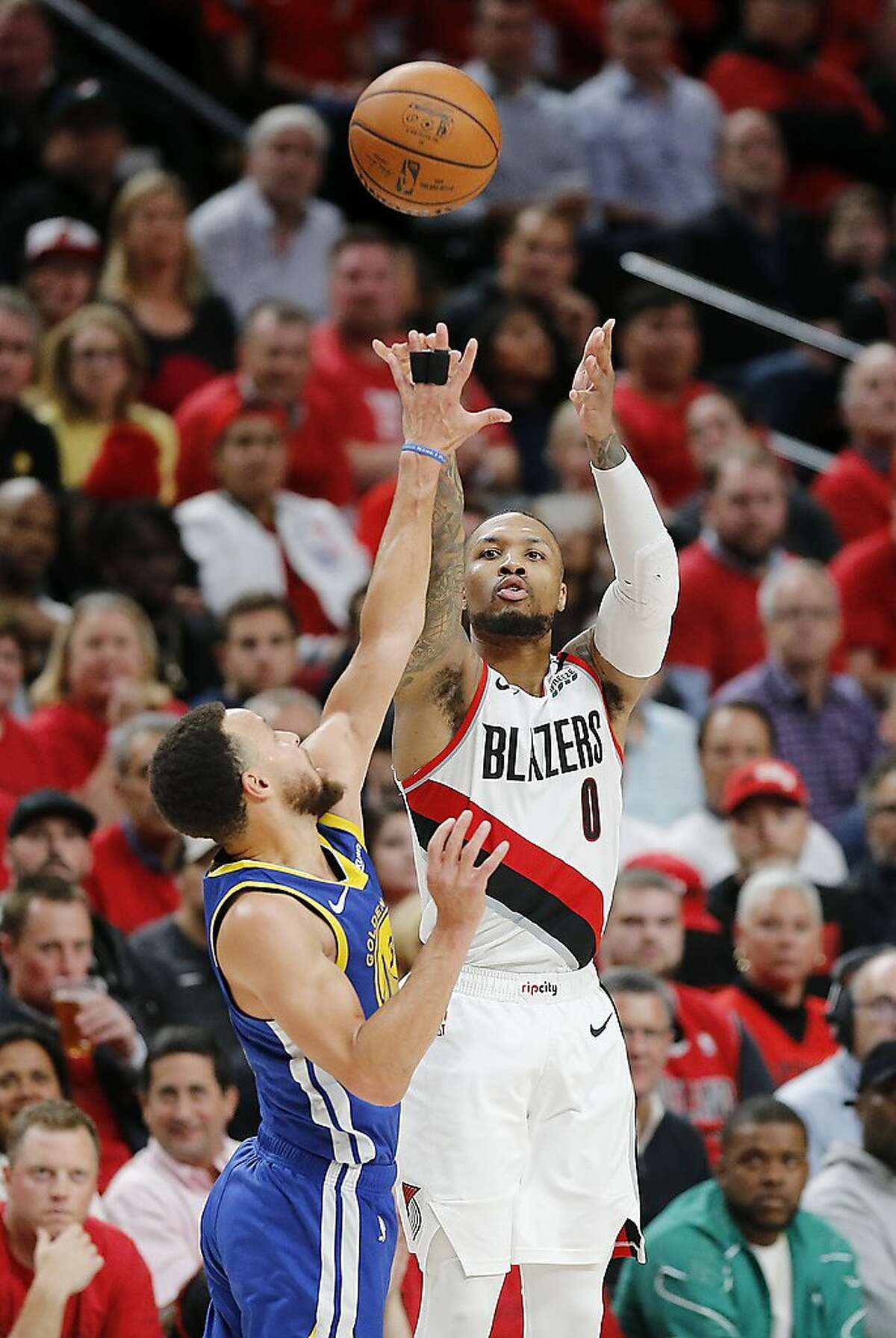 PORTLAND, OREGON - MAY 20: Damian Lillard #0 of the Portland Trail Blazers shoots the ball against Stephen Curry #30 of the Golden State Warriors during the second half in game four of the NBA Western Conference Finals at Moda Center on May 20, 2019 in Po