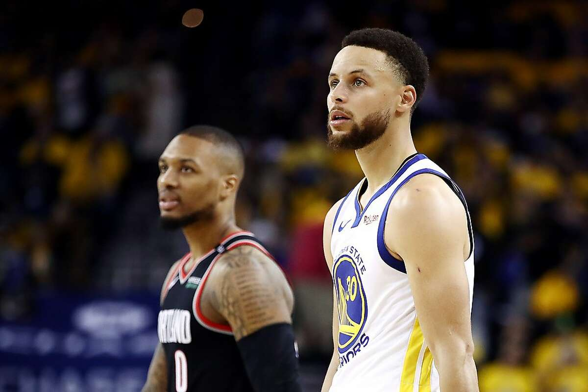 Damian Lillard (left) of the Trail Blazers and Stephen Curry of the Warriors look on during the