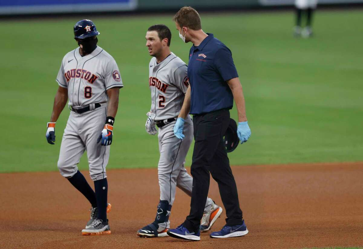 Houston Astros' Alex Bregman, center, is led off the field after he was injured while legging out a double hit off Colorado Rockies starting pitcher Ryan Castellani in the fourth inning of a baseball game Wednesday, Aug. 19, 2020, in Denver. (AP Photo/David Zalubowski)