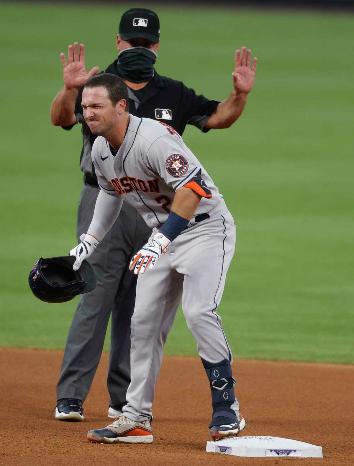 Houston Astros' Alex Bregman grimaces as he reaches second base after hitting a double in the fourth inning of a baseball game Wednesday, Aug. 19, 2020, in Denver. Bregman was removbed from the game before play resumed. (AP Photo/David Zalubowski)
