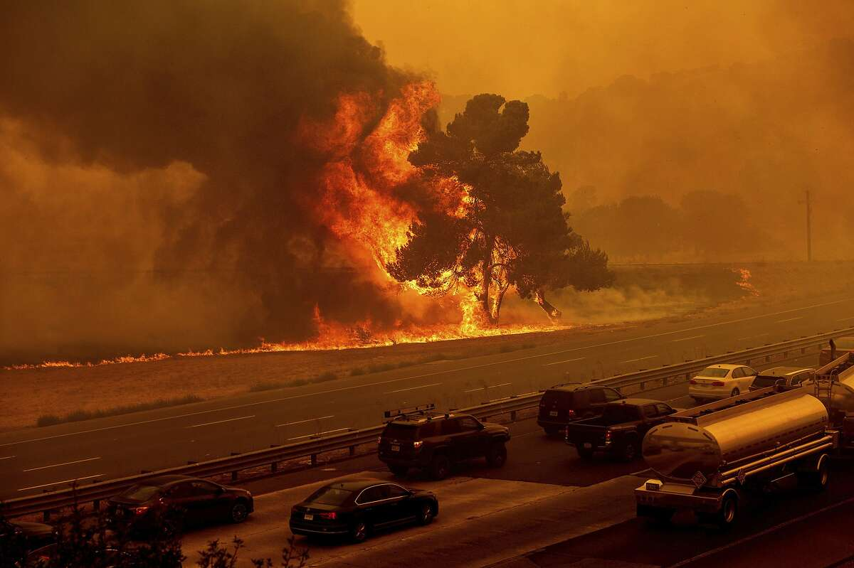 Flames from the LNU Lightning Complex fires jump Interstate 80 in Vacaville, Calif., Wednesday, Aug. 19. The highway was closed in both directions shortly afterward. Fire crews across the region scrambled to contain dozens of wildfires sparked by lightning strikes as a statewide heat wave continues.