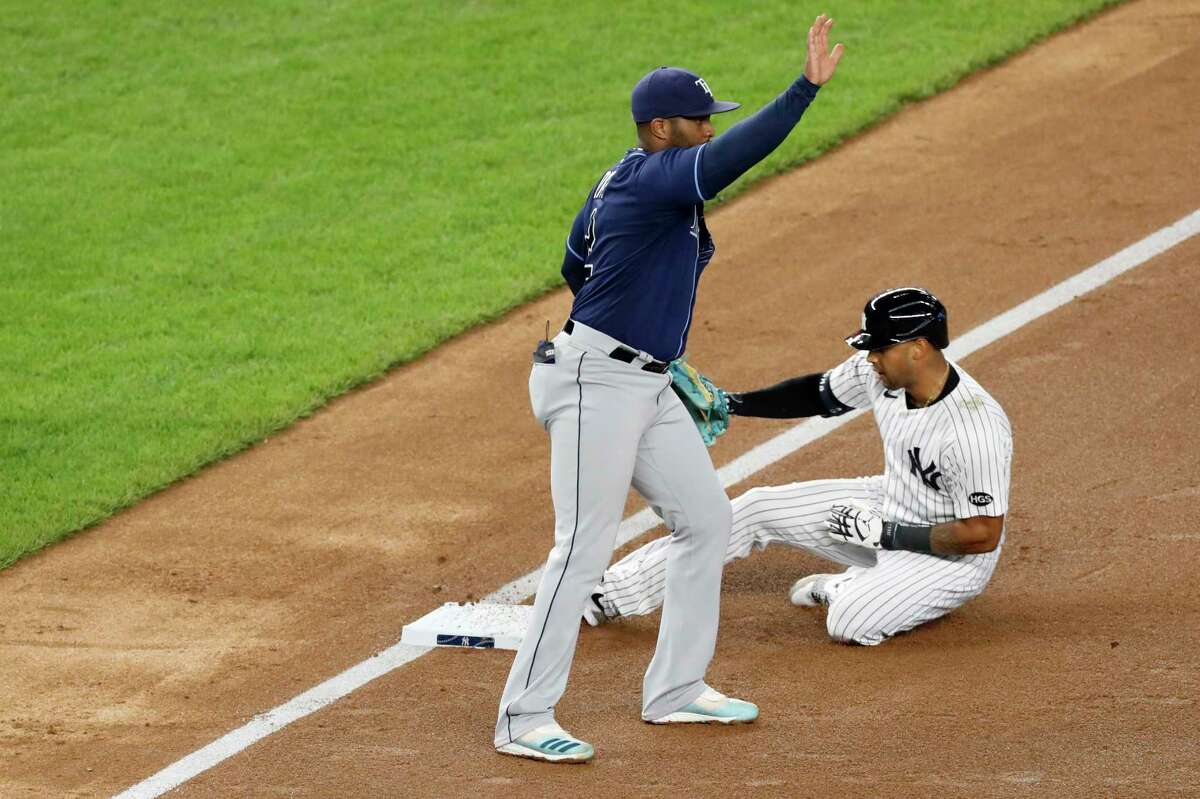 New York Yankees Aaron Hicks, right, slides into third with a triple during the sixth inning of a baseball game against the Tampa Bay Rays, Wednesday, Aug. 19, 2020, in New York. Rays third base coach Rodney Linares signals, left. (AP Photo/Kathy Willens)