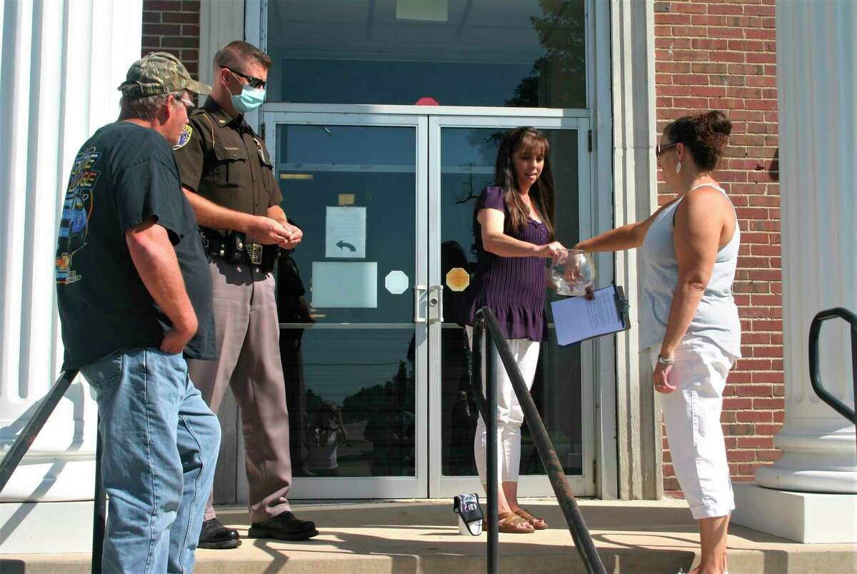 """Jeff Jurik (far left), husband of candidate Crystal Jurik, under sheriff Wes Bierling and Lake County clerk and register of deeds Patti Pacola watch as Amanda Bailor pulls a crumpled paper from a jar. Bailor pulled the paper saying """"NOMINATED"""" and was declared the winner of the August primary election. She will now move on to the November election. (Star photo/Cathie Crew)"""