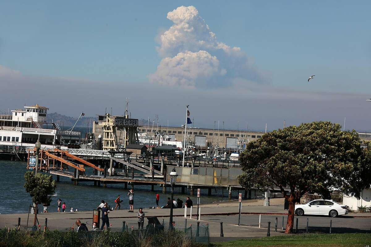 A plume of smoke can be seen in the north bay from Aquatic Park on Wednesday, Aug. 19, 2020, in San Francisco, Calif.