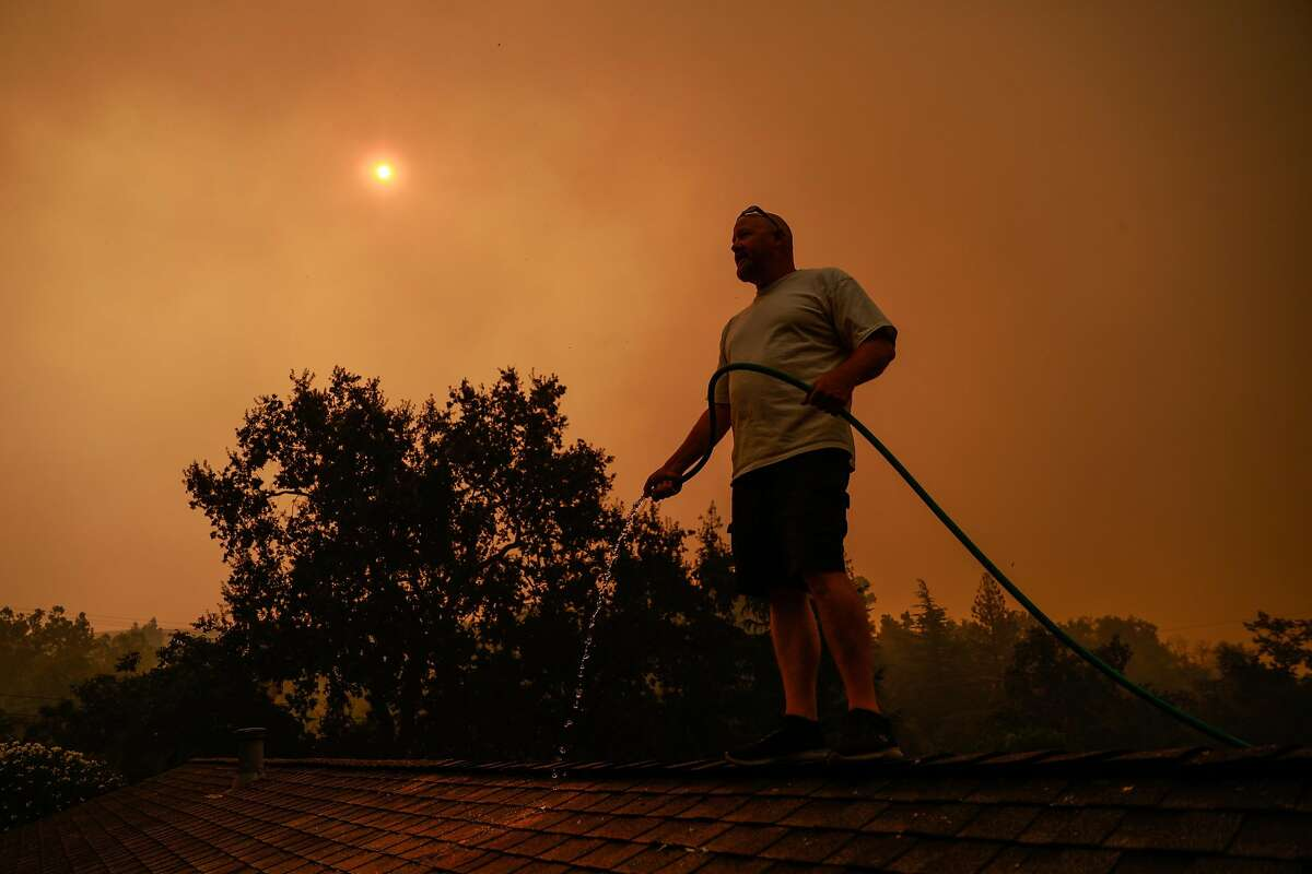 Tim Plowman waters down a friends home as he tries to save it from impending fire before evacuating the LNU Lightning Complex Fire in Vacaville , Calif., on Wednesday, August 19, 2020.