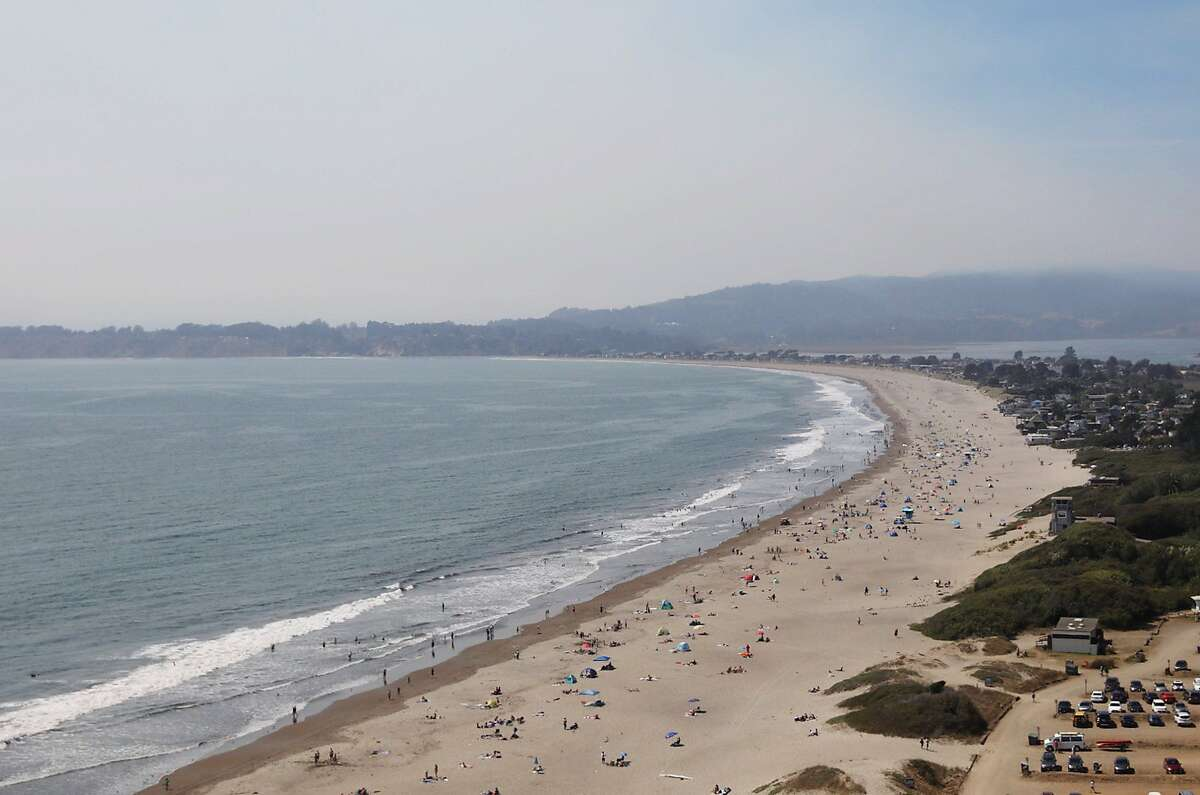 Crowds gather on Stinson Beach as smoke from the Woodward Fire in Point Reyes lingers overhead in Stinson Beach, Calif. Wednesday, August 19, 2020.