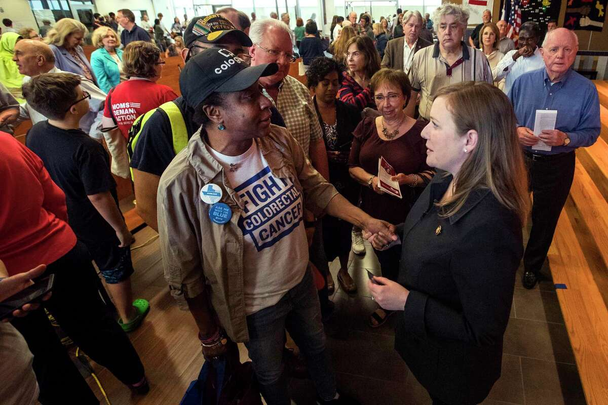 Paula Chambers, let, speaks to Rep. Lizzie Fletcher, D-Texas, following Fletcher's first town hall meeting at Frostwood Elementary School on Saturday, March 23, 2019, in Houston.