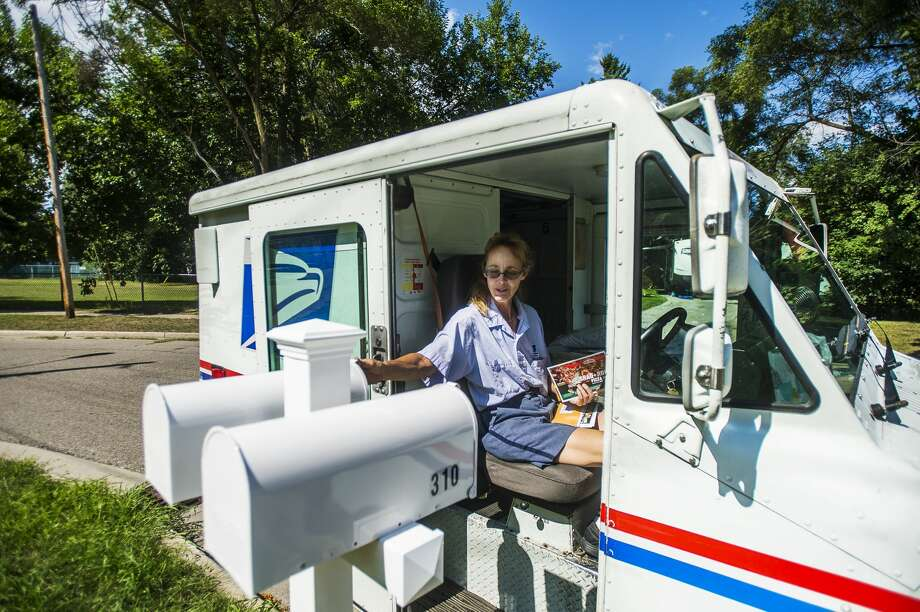 Pat Graber, a mail carrier with the USPS, delivers mail Monday afternoon, Aug. 17, 2020 in Midland. (Katy Kildee/kkildee@mdn.net) Photo: (Katy Kildee/kkildee@mdn.net)