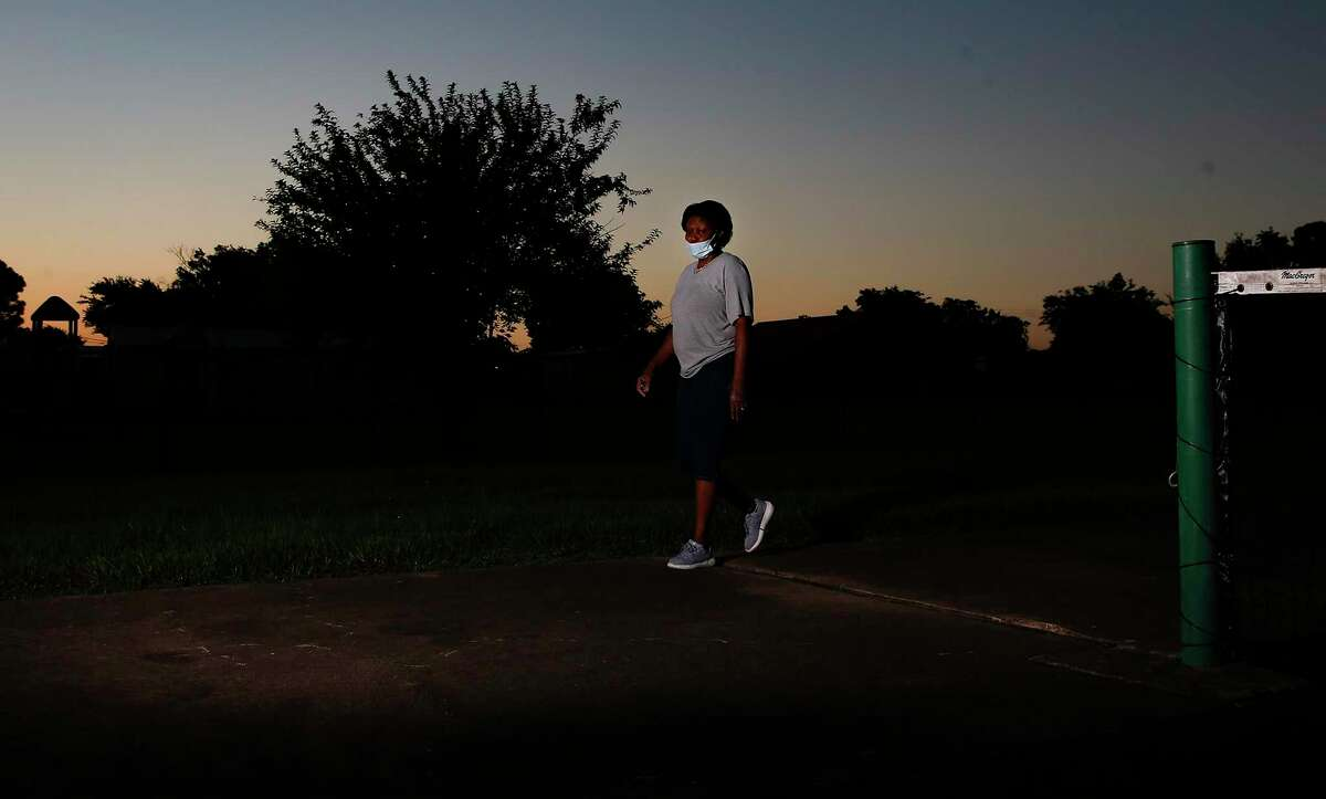 Paula Parker walks around the tennis courts at a school near her home in Houston.