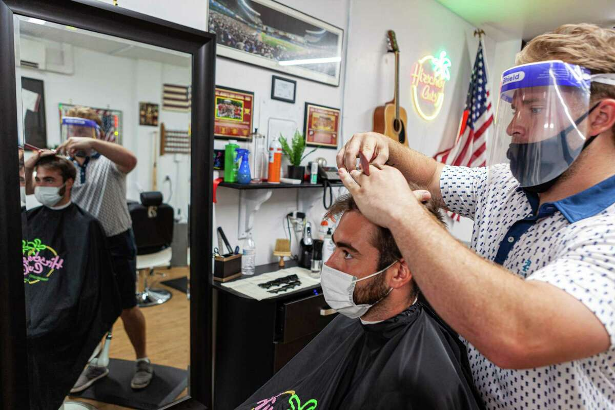 Mark Hirschbeck, owner of Hirschey Cuts on Center Street in Shelton, shows off his barbering skills.