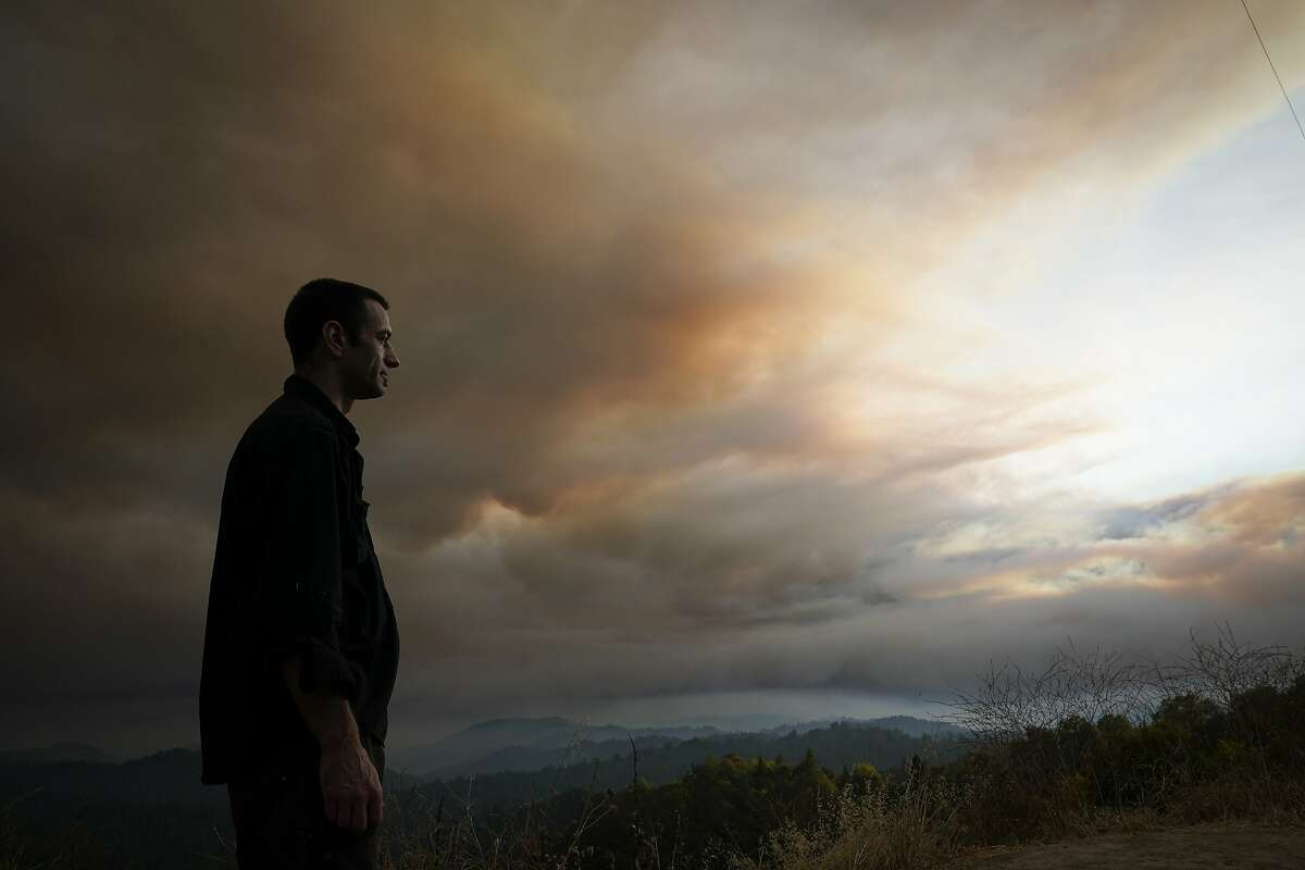 Nick Stone watches smoke from the CZU August Lightning Complex fire fill the sky in the Santa Cruz Mountains Thursday, Aug. 20, 2020, near Boulder Creek, Calif. (AP Photo/Marcio Jose Sanchez)
