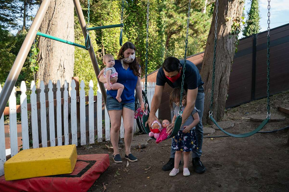 Grace, left, and Alex Sobieski play with their daughters, Desiree and Josie in the backyard of their home in Pacifica, Calif., on Sunday, Aug. 16, 2020. The Sobieski's built a play structure in their backyard, since parks are closed due to the coronavirus.