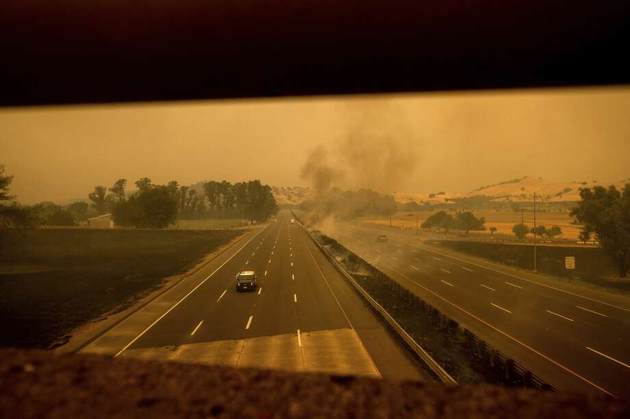 A police vehicle drives along Interstate 80, which was closed when flames from the LNU Lightning Complex fires jumped the roadway, in Vacaville, Calif., on Wednesday, Aug. 19, 2020. Photo: Noah Berger/Associated Press / Noah Berger