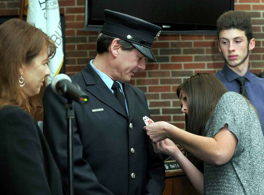 File photo from when Danbury Firefighter Ray Guard was promoted to the position of Fire Lieutenant in a ceremony at Danbury City Hall Thursday, Feb. 8, 2018. Pinning his lieutenants badge on is daughter Brittany, 24. Left is fiance Dagmar Langevin. Right is son Ray, 18. Guard started with the Danbury Fire Department in 2005 after a career as an electrician. Photo: Carol Kaliff / Hearst Connecticut Media / The News-Times
