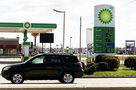 Fuel prices are displayed on a sign outside a BP gas station in Appleton, Wis., on April 20, 2020. International oil majors like BP and Chevron have eliminated thousands of jobs.