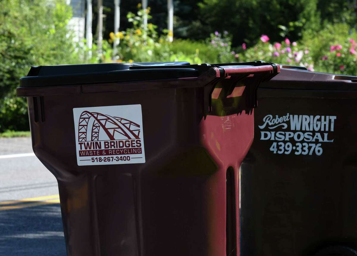 Trash cans from Twin Bridges Waste & Recycling and Robert Wright Disposal are seen along Kenwood Avenue on Thursday, Aug. 20, 2020, in Bethlehem, N.Y. Trash companies are in the midst of a marketing fight for suburban Capital Region customers. Twin Bridges recently offered a year of free trash pickup for new customers in Delmar. (Will Waldron/Times Union)