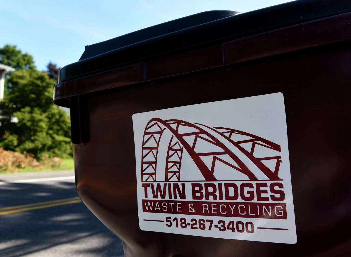 A trash can from Twin Bridges Waste & Recycling is seen along Kenwood Avenue on Thursday, Aug. 20, 2020, in Bethlehem, N.Y. Trash companies are in the midst of a marketing fight for suburban Capital Region customers. Twin Bridges recently offered a year of free trash pickup for new customers in Delmar. (Will Waldron/Times Union)