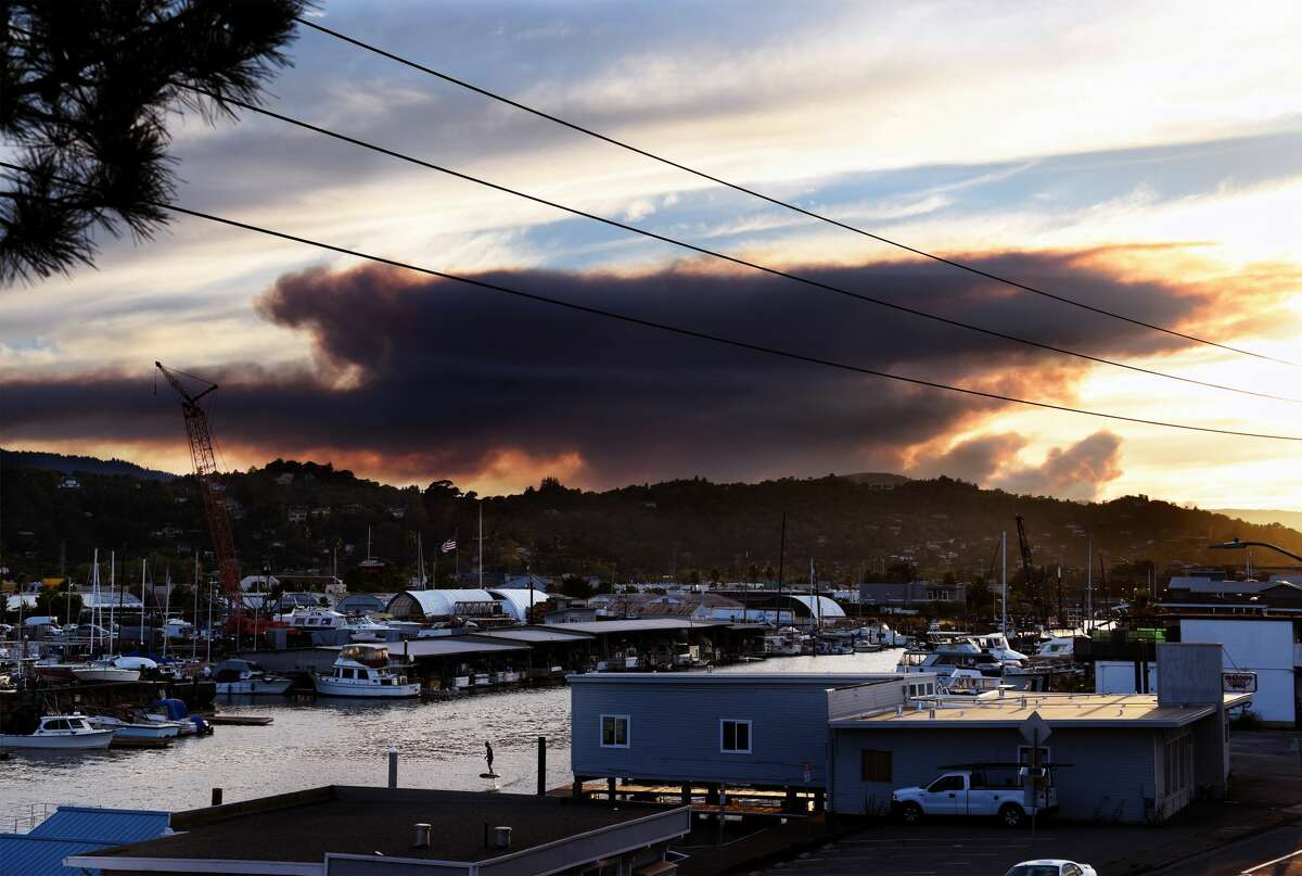 At sunset, a giant plume of smoke from Woodward Fire in a remote area of the Point Reyes National Seashore is seen as it rises above the horizon in San Rafael, Calif. on Tuesday, Aug. 18, 2020. The wildfire burned at least 700 acres was at zero percent containment as of 9 p.m.