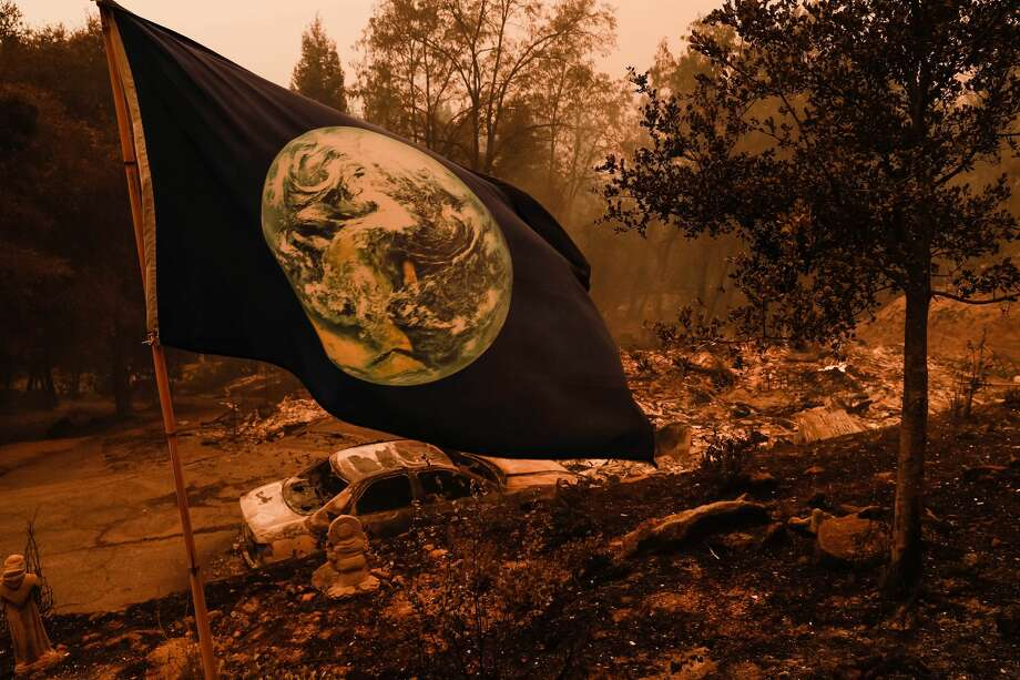 A flag with the earth on it is one of the few things left untouched at a home that was burned to the ground on Pine Flat Road in Bonny Doon, Calif., on Wednesday, Aug. 19, 2020. Photo: MediaNews Group/The Mercury News/MediaNews Group Via Getty Images / Bay Area News Group - Digital First Media