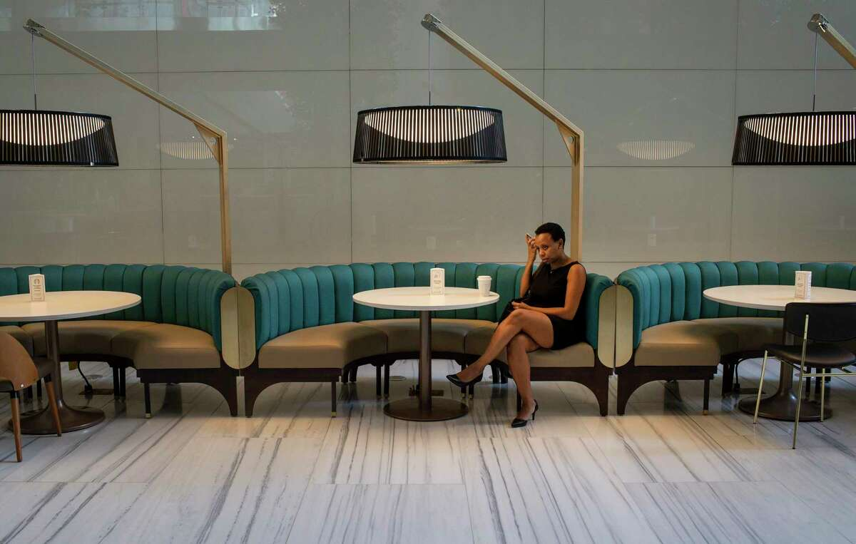 """Iva Mendes talks on the phone Tuesday, Aug. 4, 2020, at Understory, a food court connected to the downtown tunnels, in Houston. """"Downtown looks like Sunday every day,"""" she said."""