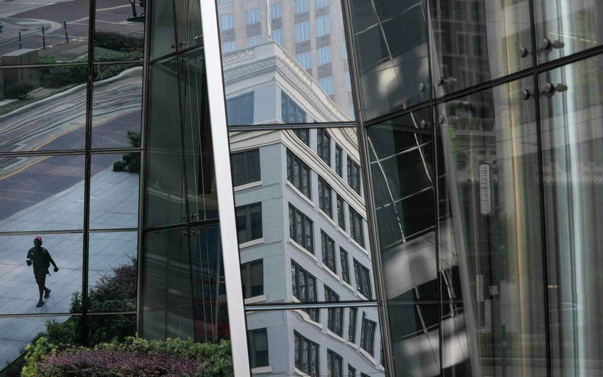 A man, reflected in the windows of the 609 Main at Texas building, walks along Main Street on Monday, Aug. 3, 2020, in Houston.